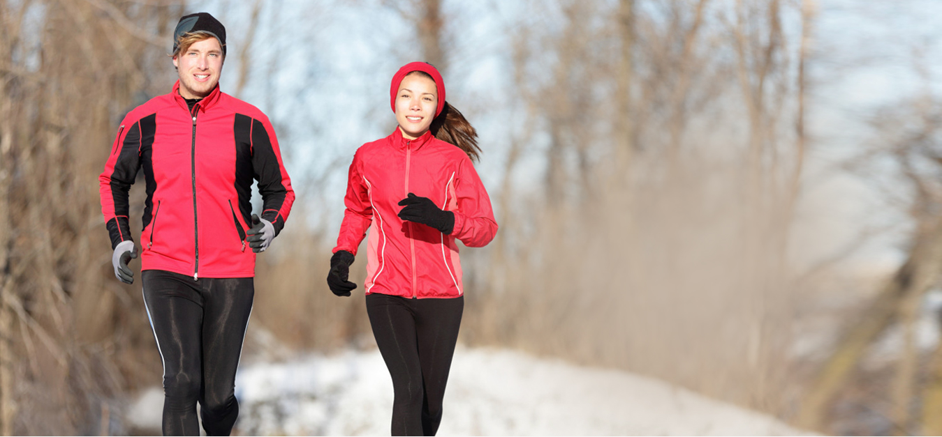 male & female runner running in snow wearing BodyWarmer Thermal Hoop inside