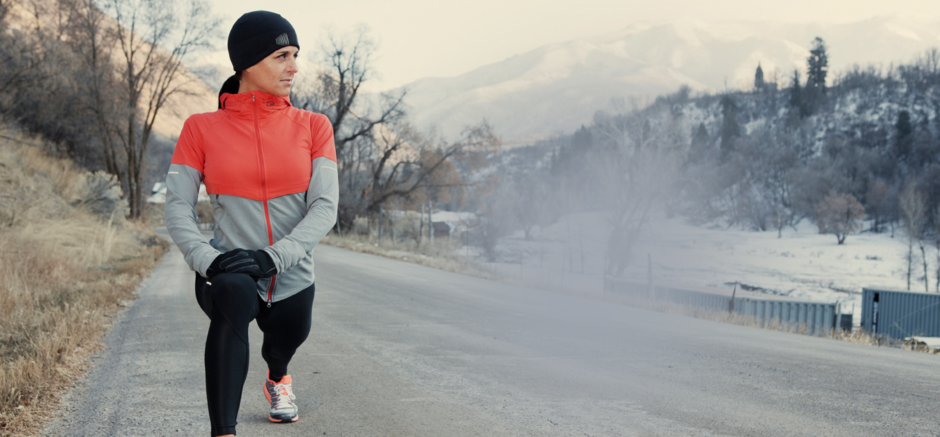 female athlete stretching out in cold with BodyWarmer Thermal Hoop inside running gear